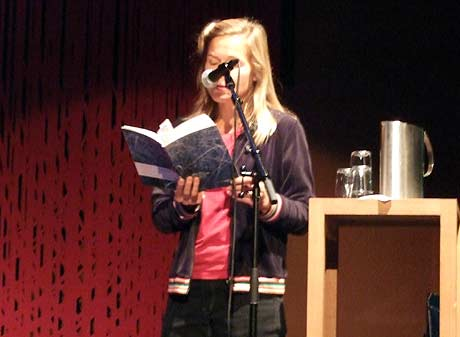 Ingvild Burkey med mikrofonen foran ansiktet på Litteraturhuset.